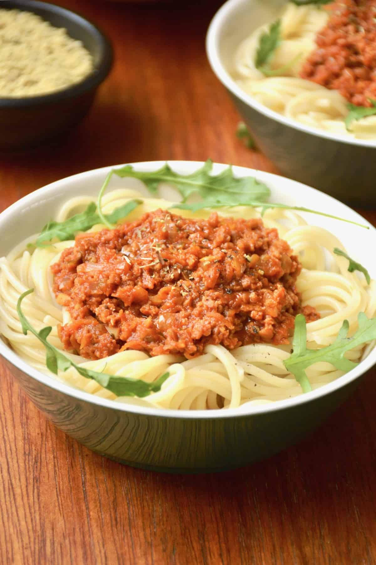 A bowl of vegan spaghetti bolognese with some decorative rocket leaves.