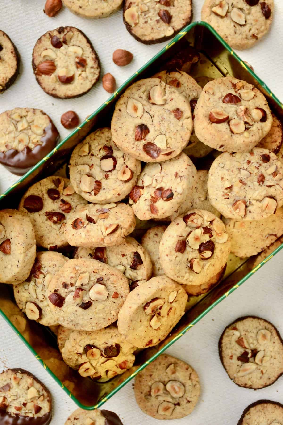 A rectangular tin full of hazelnut topped cookies.