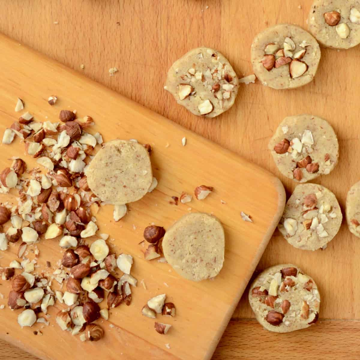 A chopping board with hazelnuts on, next to hazel topped cookies.