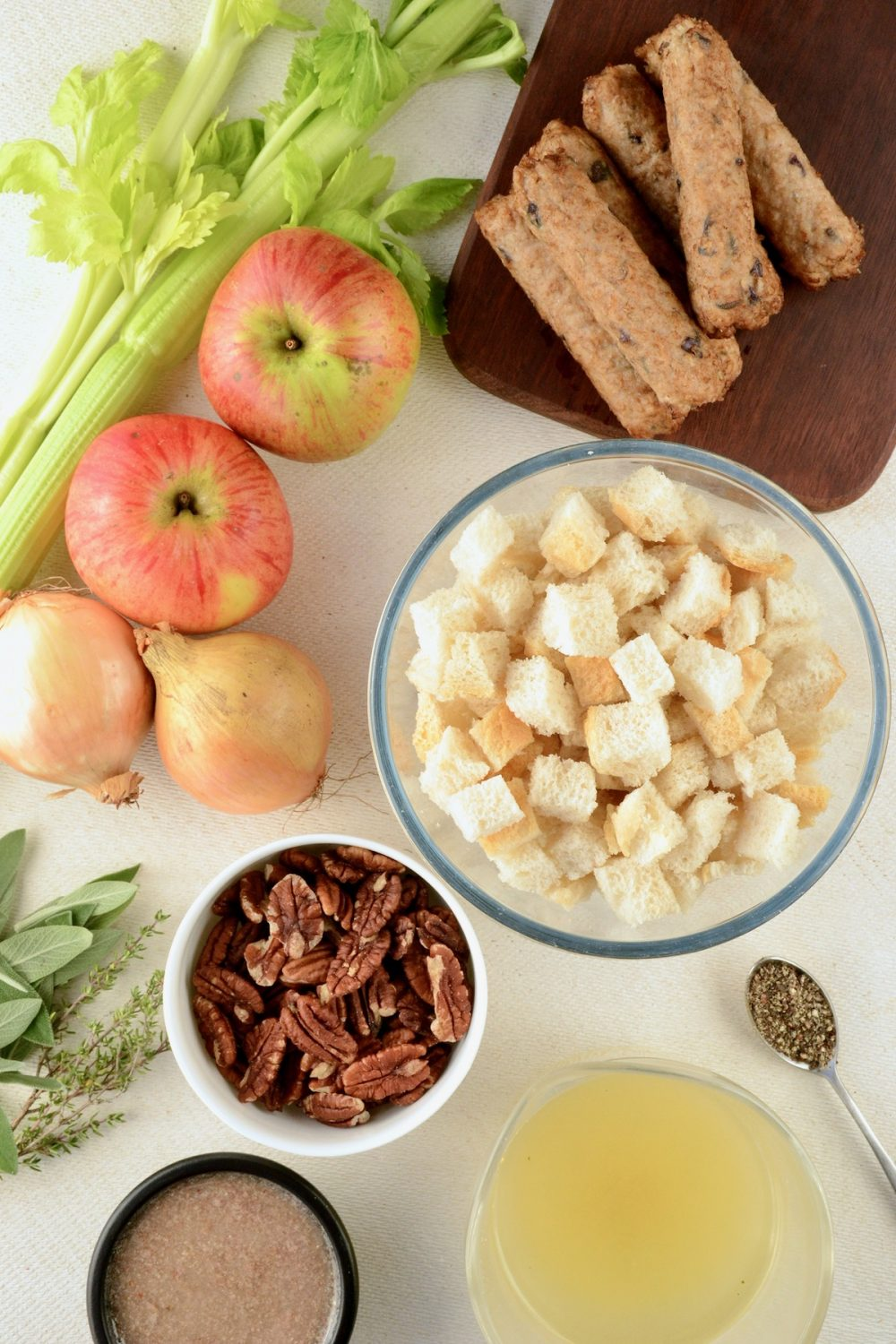 Ingredients on a board, a bowl of bread cubes, pecans, vegan sausages, apples, onions, celery, stock, herbs and flax 'egg'.