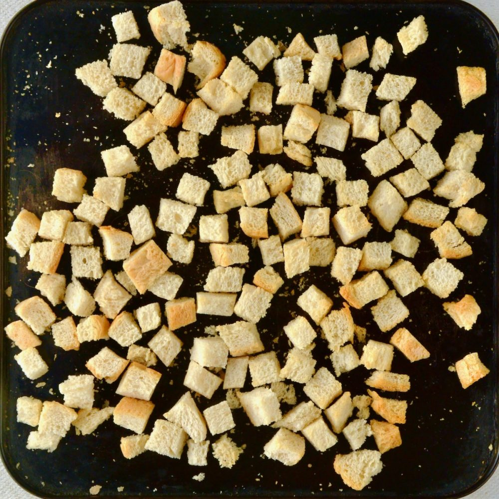 Bread cubes toasting on a baking tray.