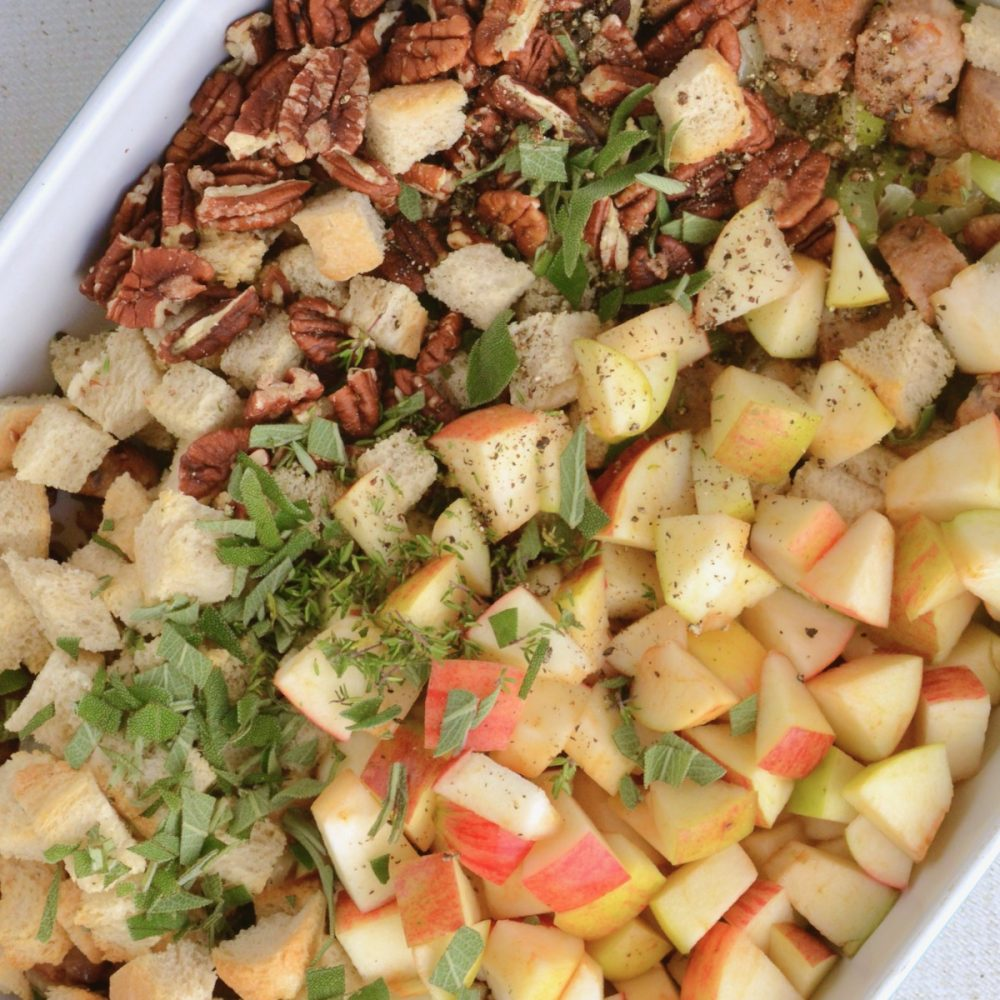 Bread cubes, apples, pecans, and herbs in an oven.