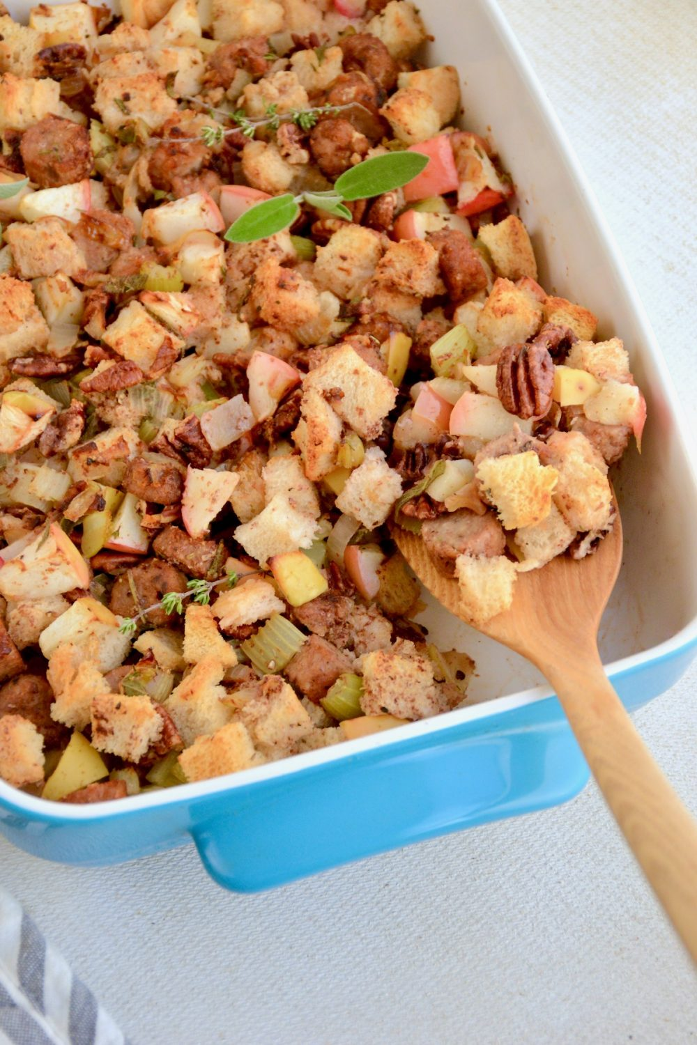 A spatula lifts a portion of stuffing from the dish.