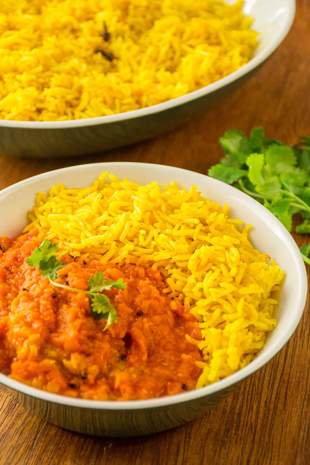 A bowl of red lentil dal and baked turmeric rice on the side.