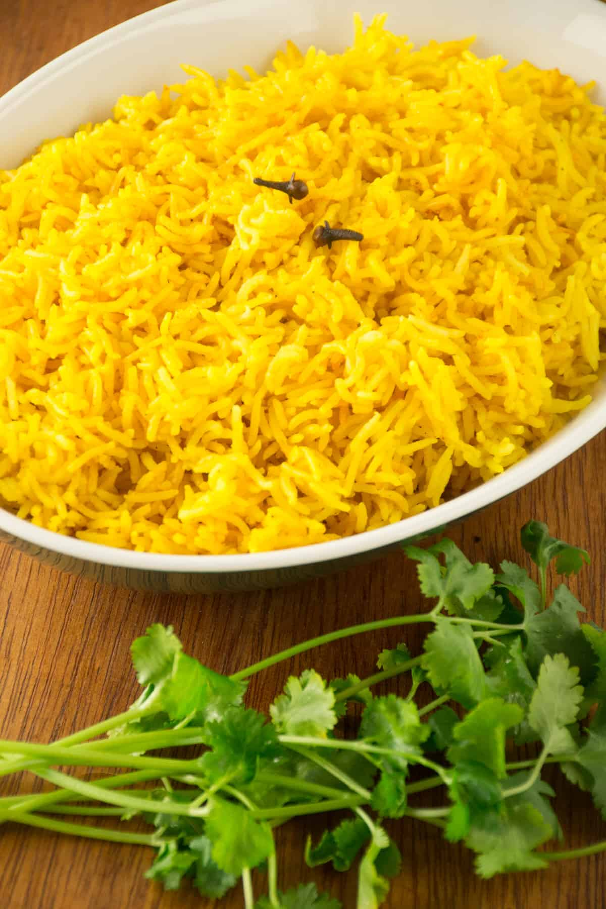 A dish of turmeric rice, with two whole cloves on top.