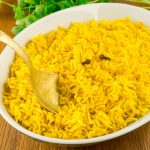 A brass spoon dips into the serving bowl of yellow rice.