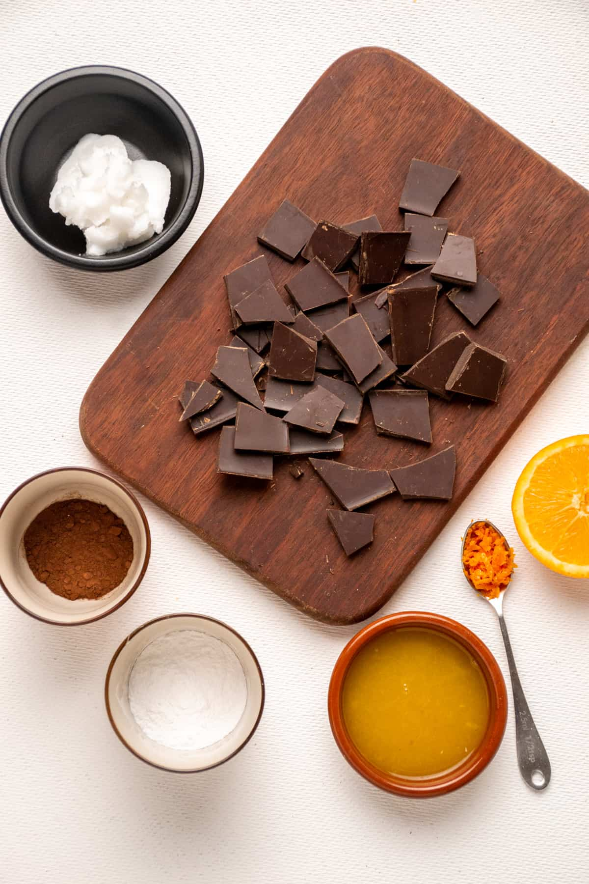 A wooden board with chocolate and small dishes containing orange juice, sugar, cocoa, coconut oil and a spoonful of zest.