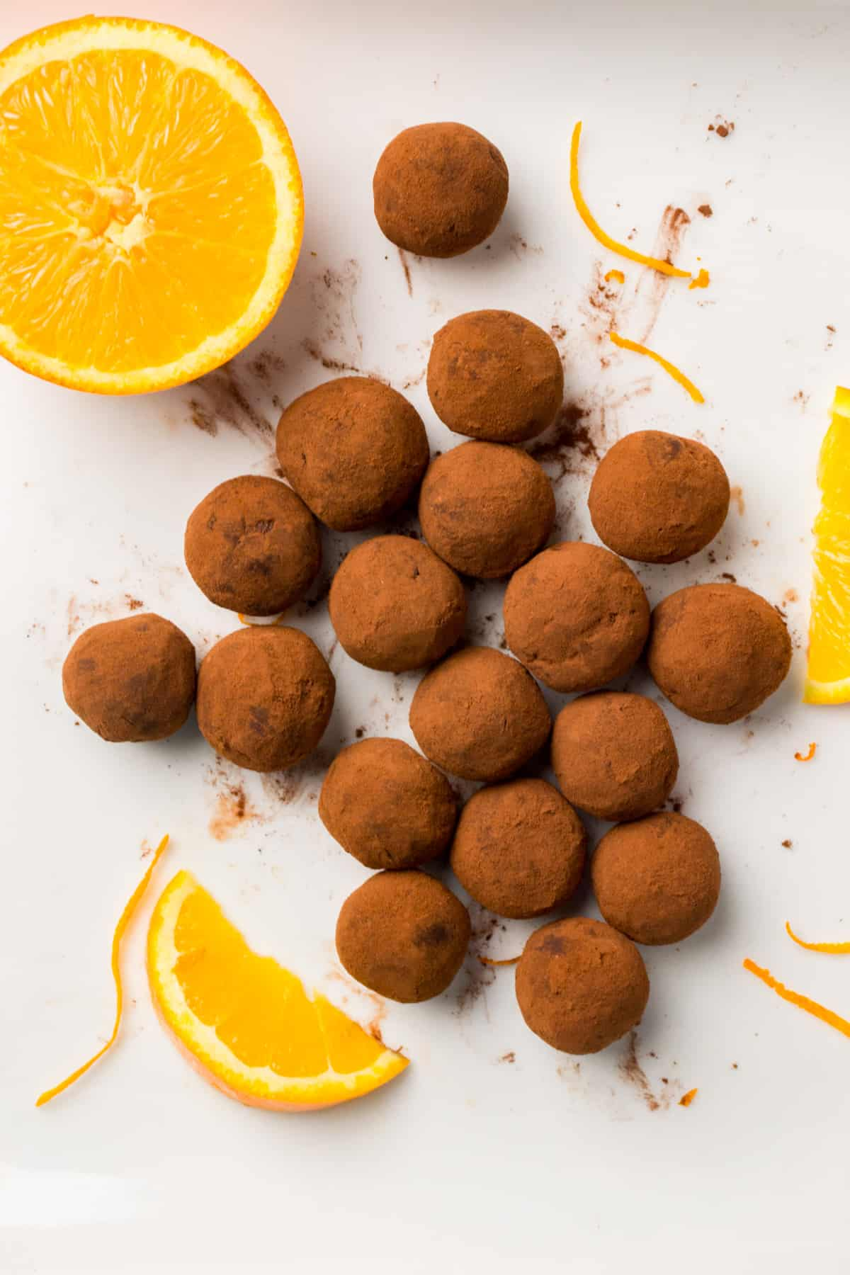 An abstract composition of truffles, oranges slices and zest on a white surface.