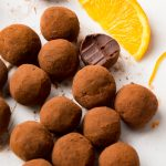 Cocoa dusted truffles next to a slice of orange. One truffle is bitteen in half to reveal the dark chocolate centre.