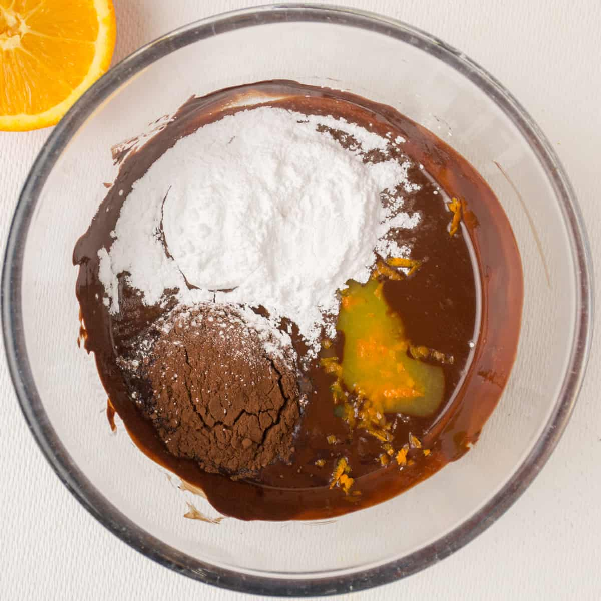 Adding sugar, cocoa, orange juice and zest to the chocolate mixture