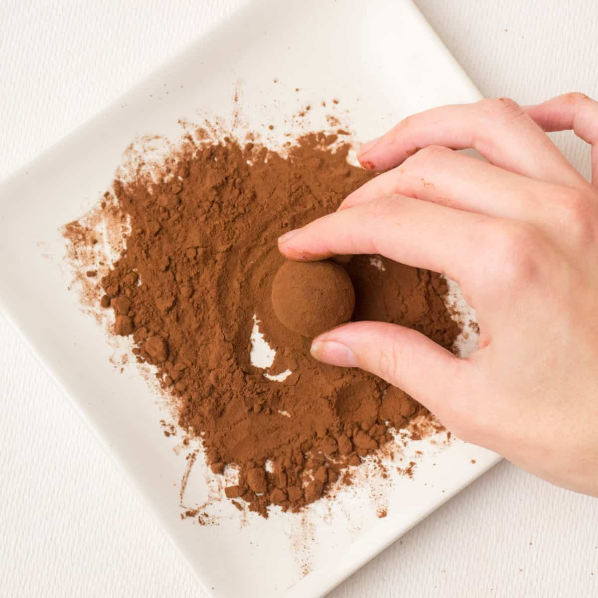 Rolling the truffle in cocoa powder on a square white plate.