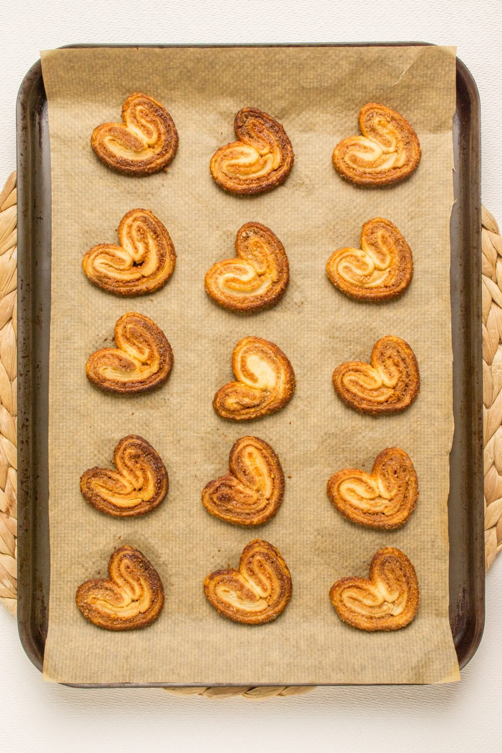 Fifteen baked cookies on a lined baking tray.