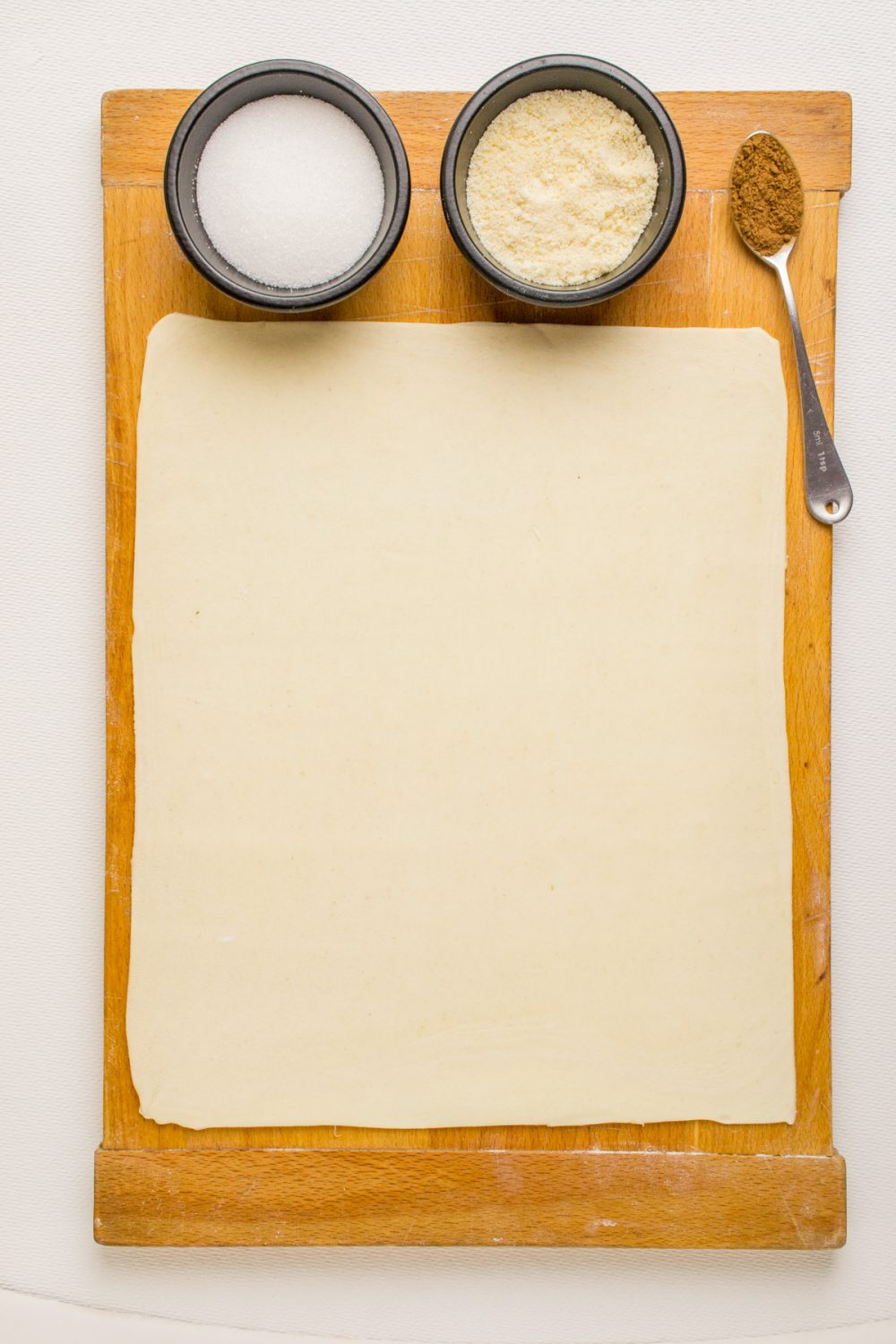 A sheet of puff pastry, small bowls of sugar and ground almonds and a spoonful of cinnamon on a wooden board.