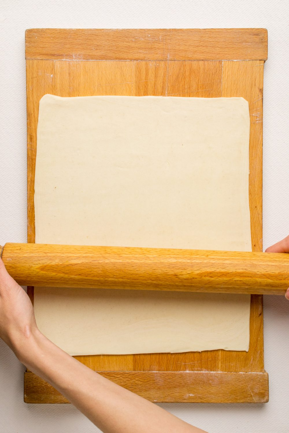 A wooden rolling pin rolls out a rectangle of puff pastry.