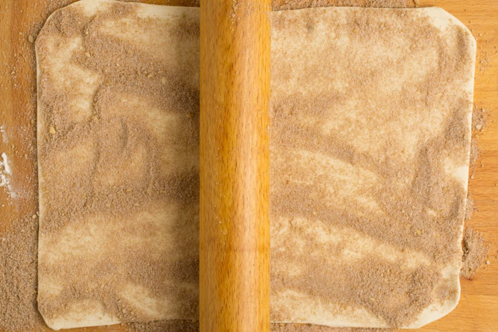 A rolling pin gently presses the sugar into the pastry.