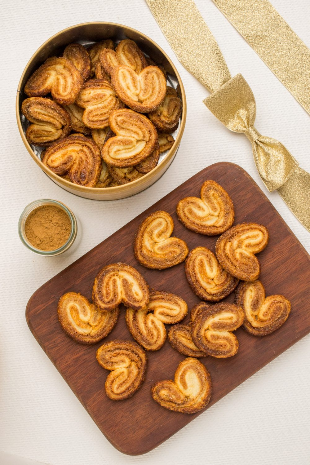 A tin full of cinnamon palmiers next to a wooden board with more cookies.