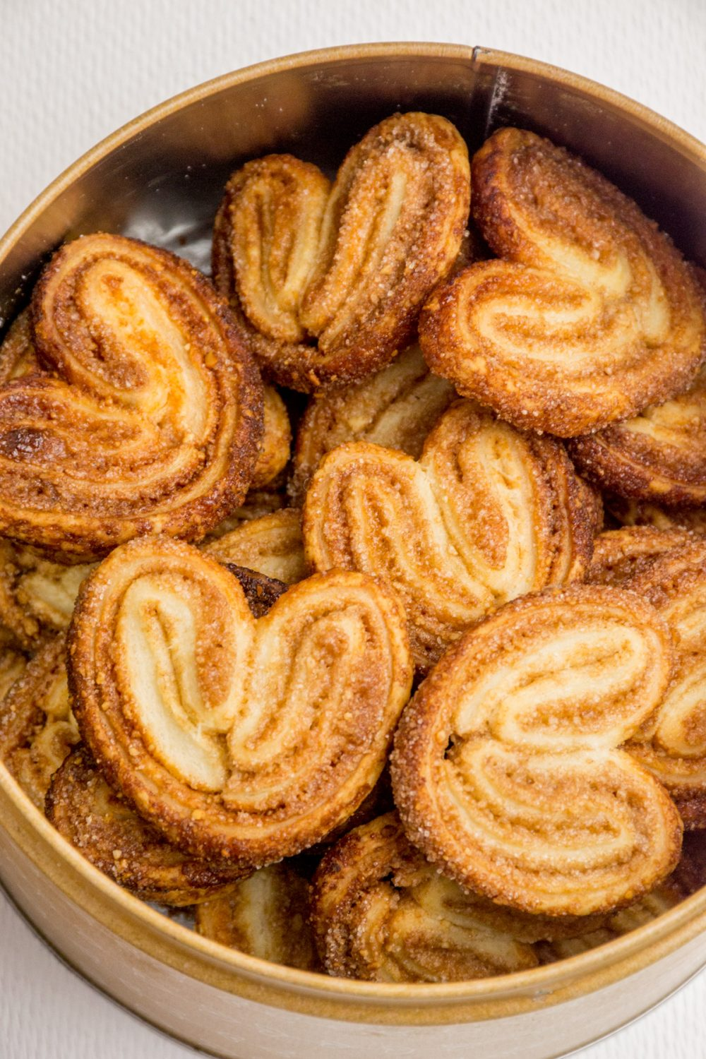 A round cookie tin full of vegan palmiers.