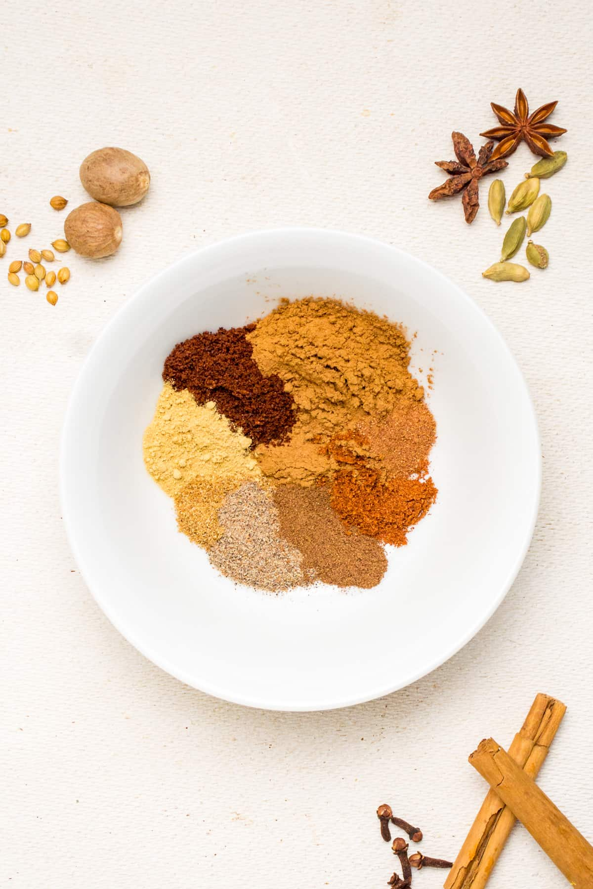 A white bowl of ground spices, whole spices on the surface around the bowl.