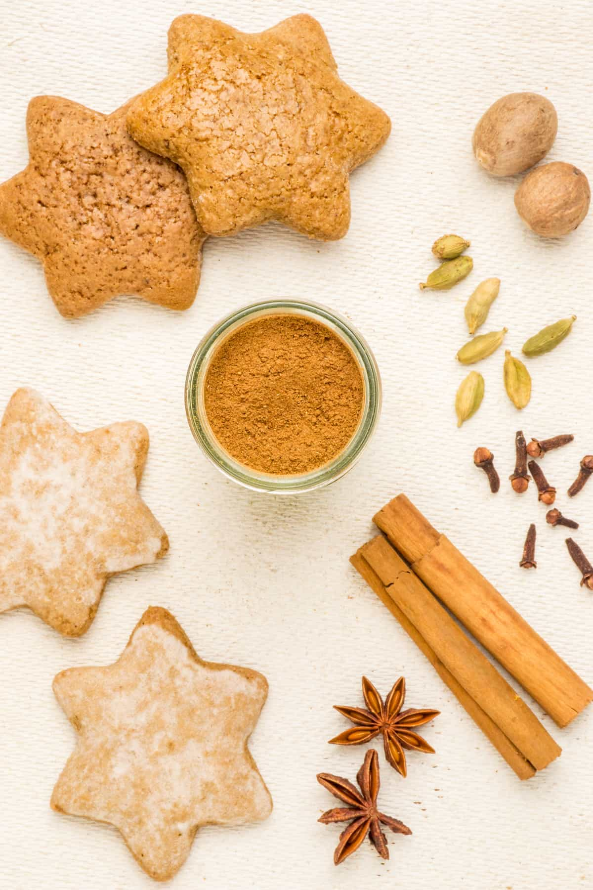 Seen from above, gingerbread spices in the centre surround by star shaped cookies and whole spices.