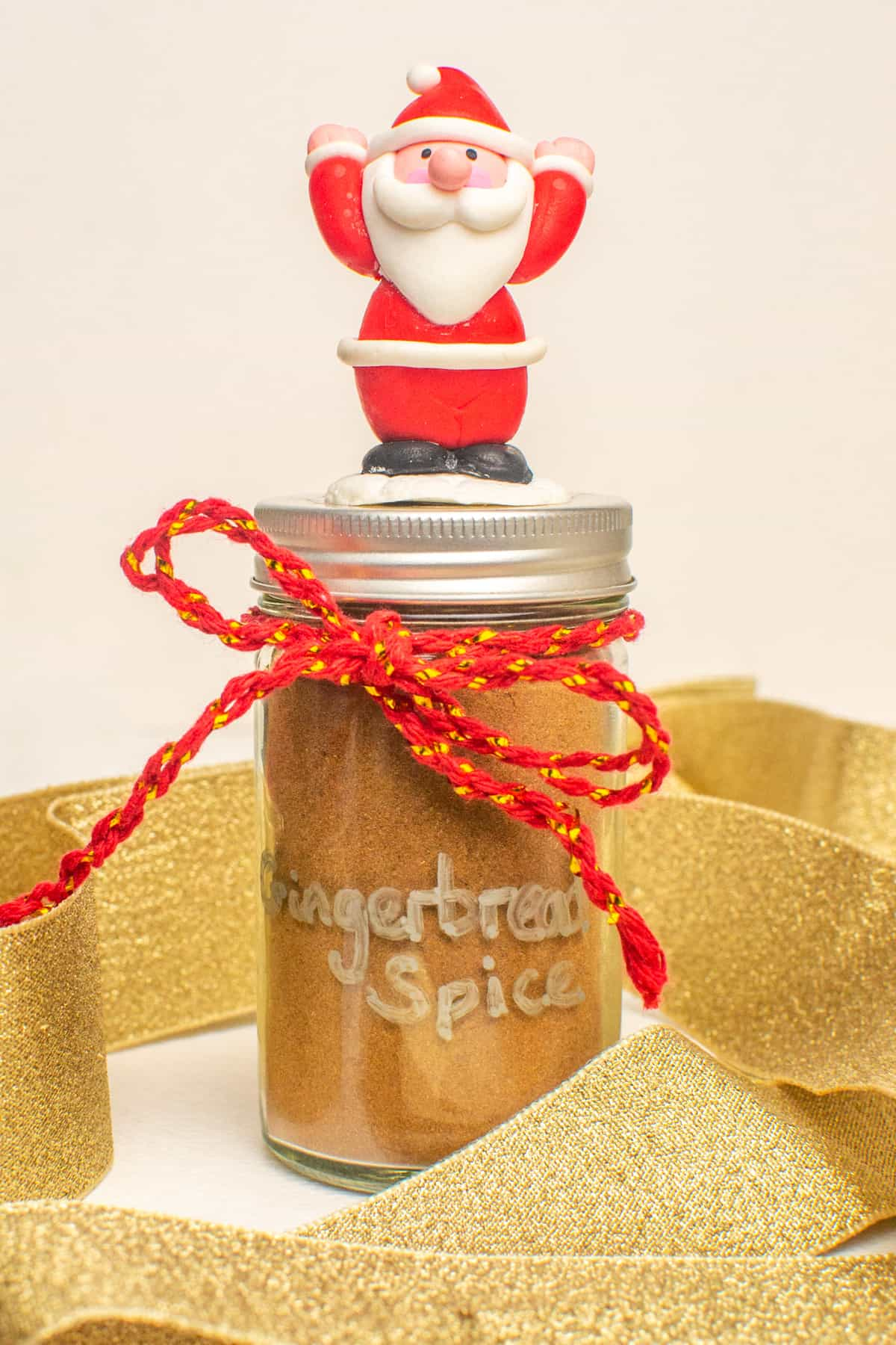 A jar of spice decorated with ribbon, twine and a small Father Christmas on top.