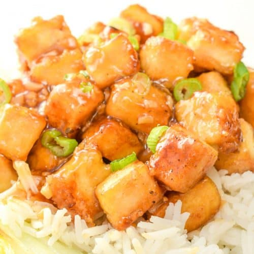 Cubes of tofu covered in a stickey lemon sauce on white rice.