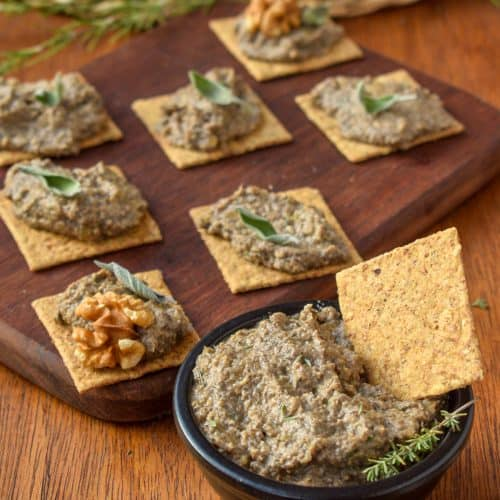 A dish of vegan mushroom pate, next to a wooden platter with pate topped crackers.