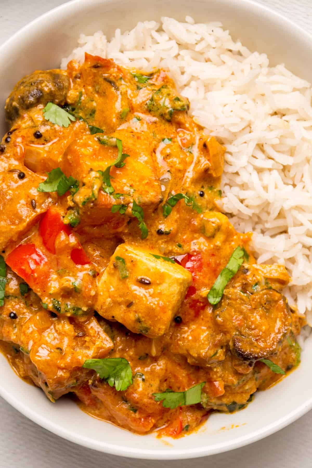 Thick curry sauce, with cubes of tofu, red pepper and mushrooms and herbs on top of some white rice.