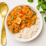 A bowl of richly coloured vegan tikka masala with rice, a brass spoon and herbs on the next to it..