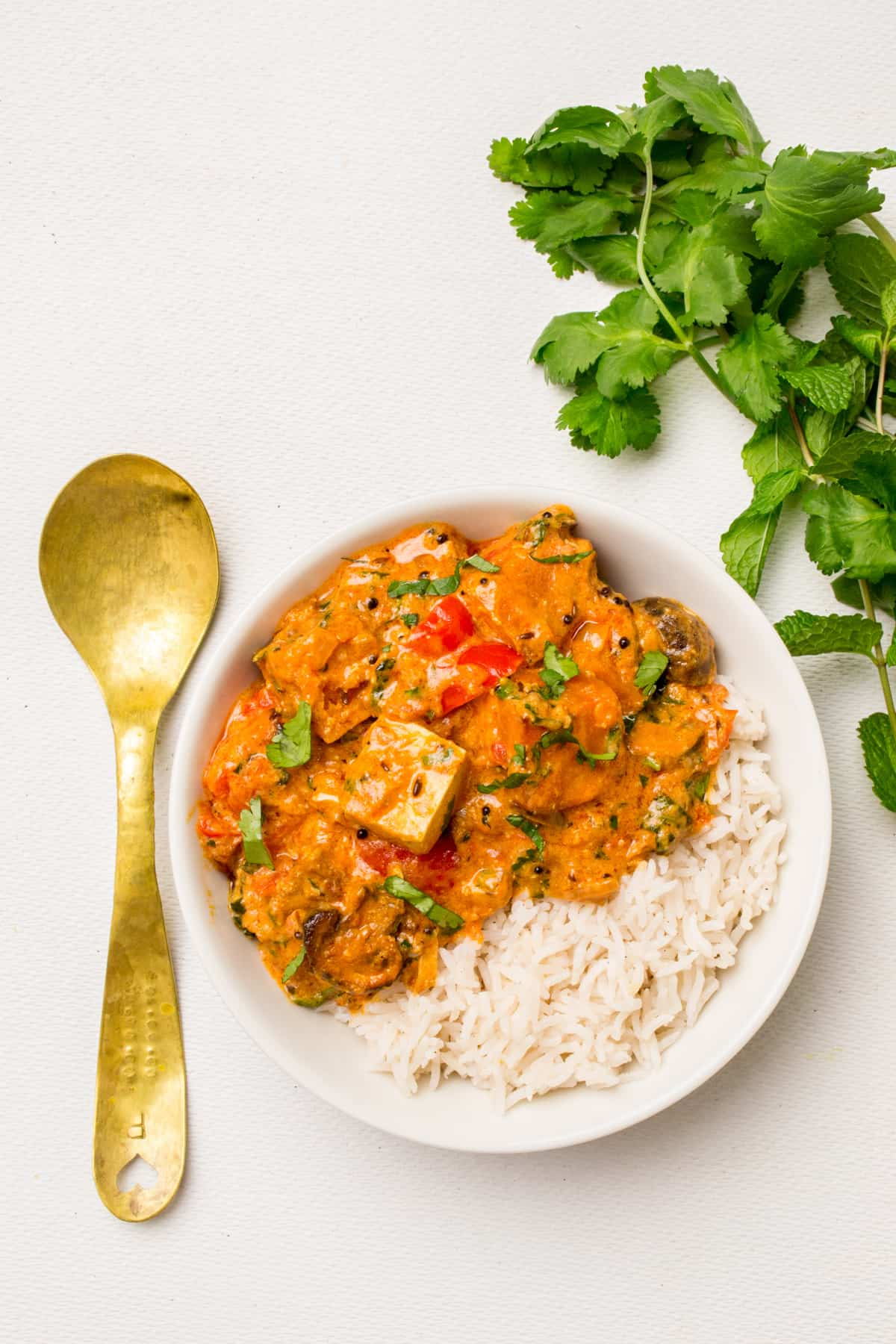 A bowl of richly coloured vegan tikka masala with rice, a brass spoon and herbs on the next to it.