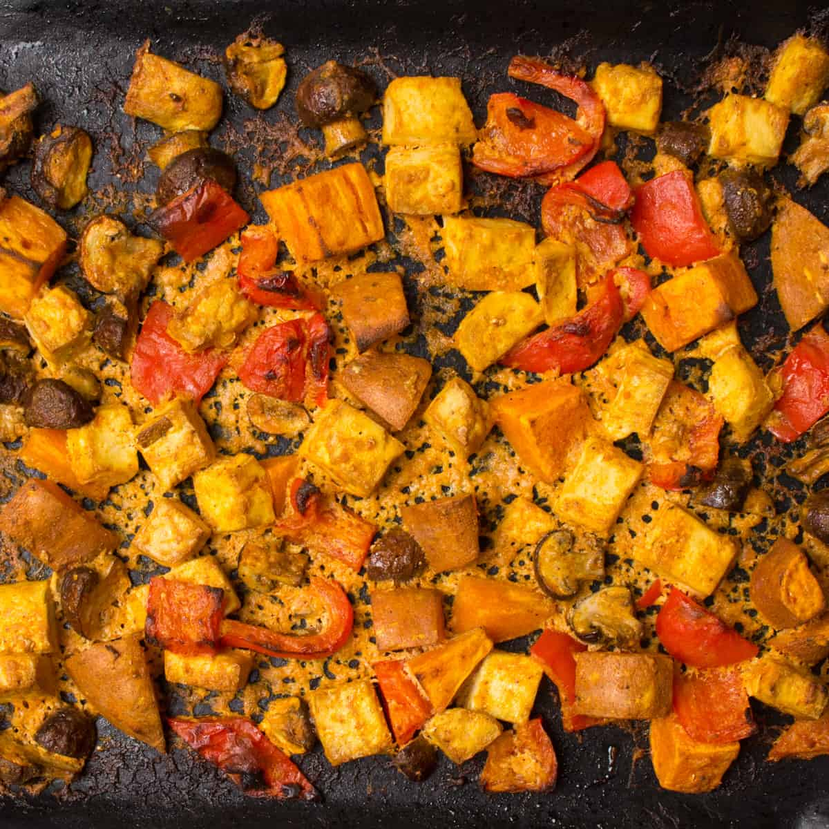The marinated veggies and tofu have been roasted on a baking tray.