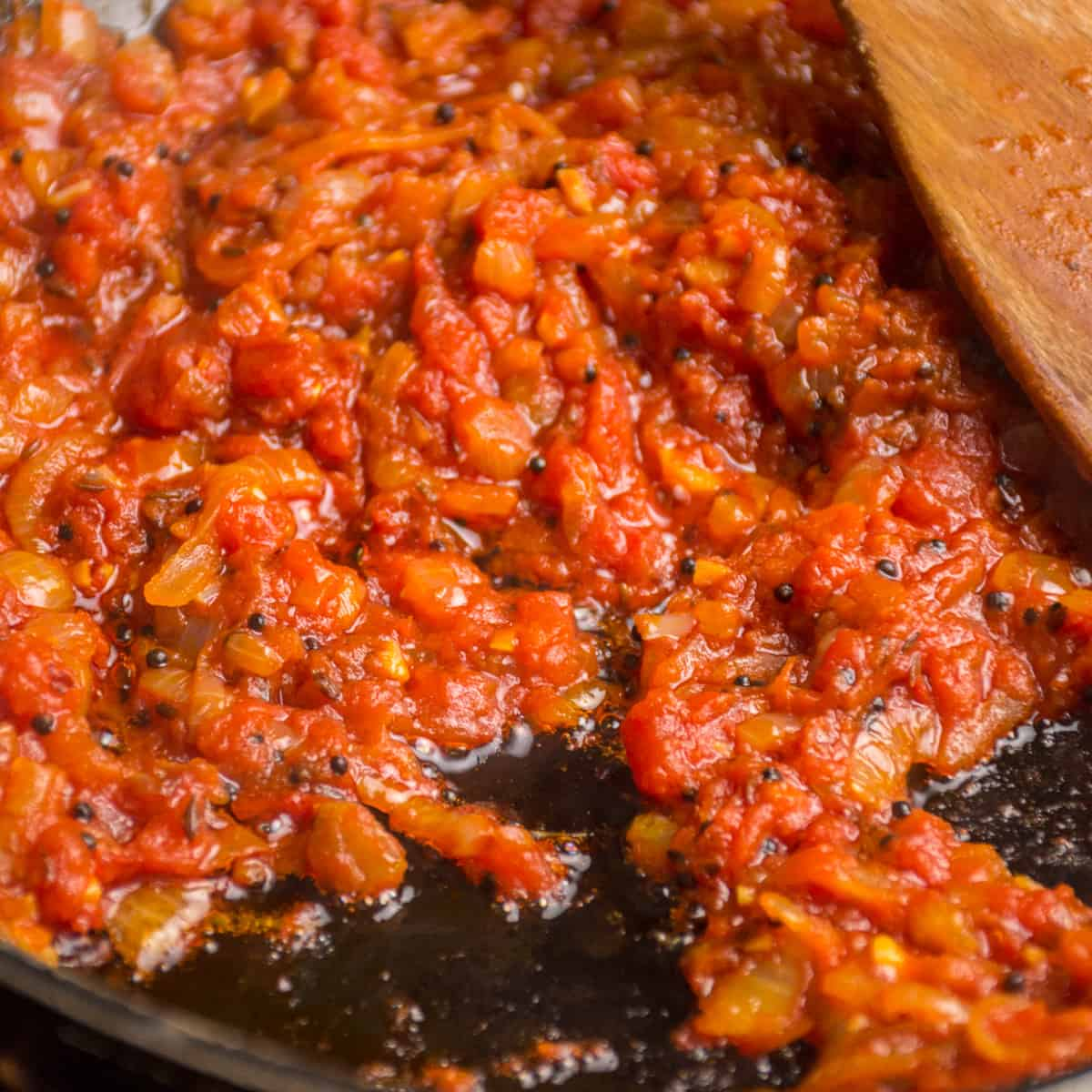 Chopped tomatoes are added to the onion and cooked until thickened.