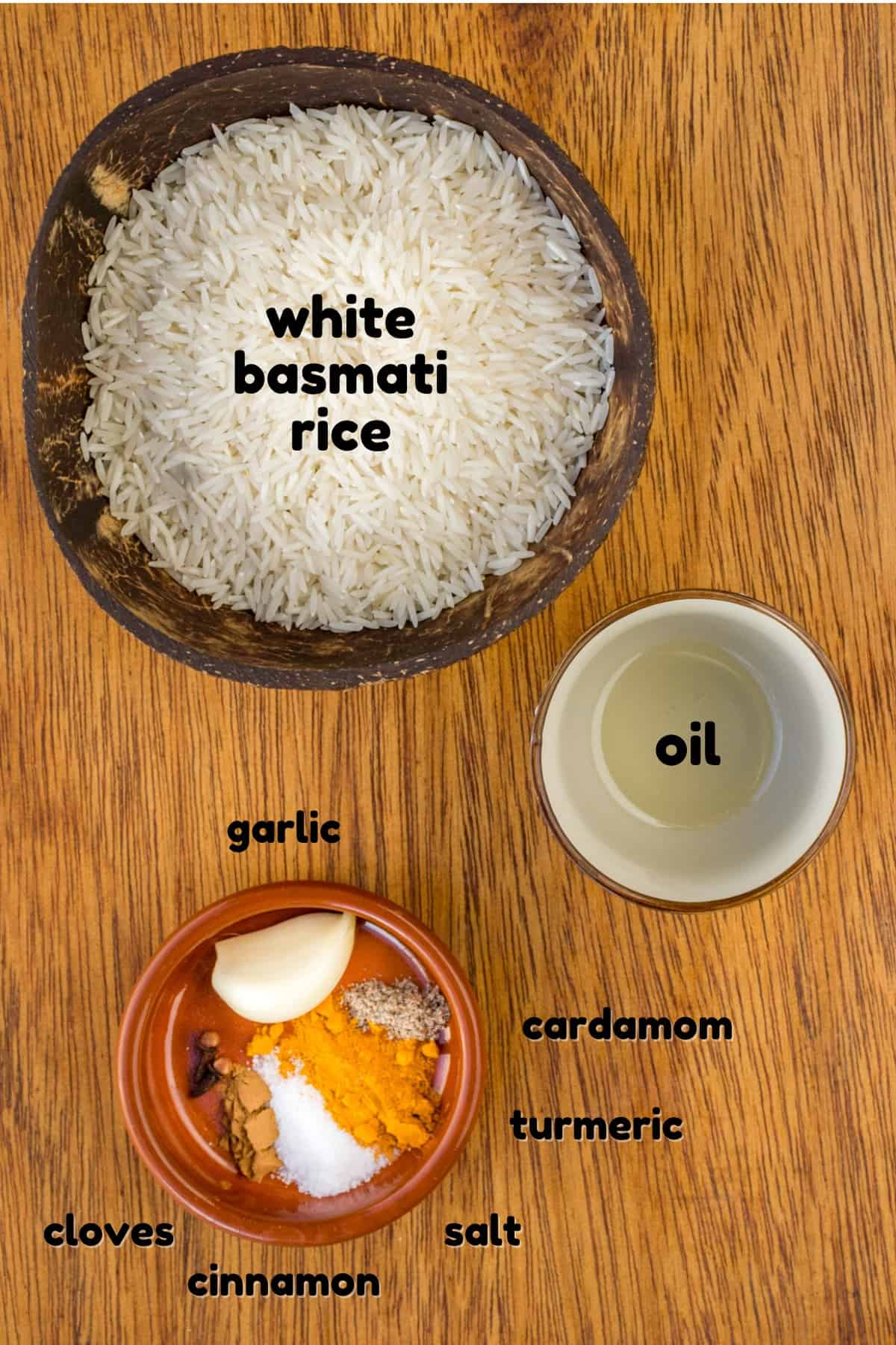 A coconut bowl of white rice, a small dish of oil, and a terracotta pot containing garlic, cardamom, turmeric, salt, cinnamon and cloves.