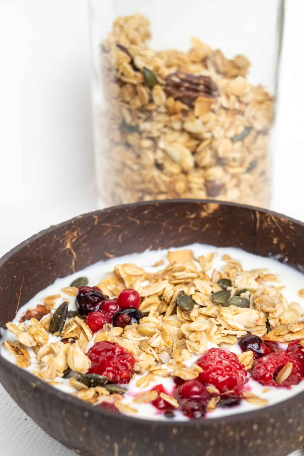 In the foreground, a coconut bowl with granola and fruit on soy yoghurt, in the background granola stored in a tall glass jar.