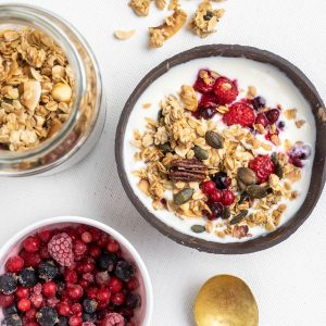 A bowl of granola with yoghurt and berries next to a jar of granola and a bowl of fruit.
