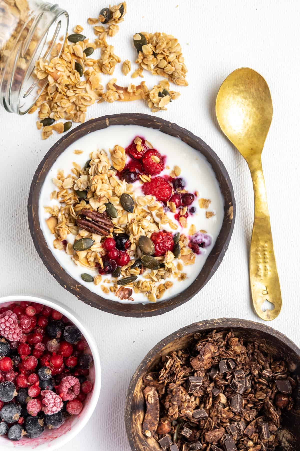 In the center, a serving of granola with red berries and soy yoghurt in a coconut bowl. Around it, cocoa and chocolate flavoured granola in another coconut bowl, a smaller bowl of red fruit, a jar from which granola spills out and a golden spoon.