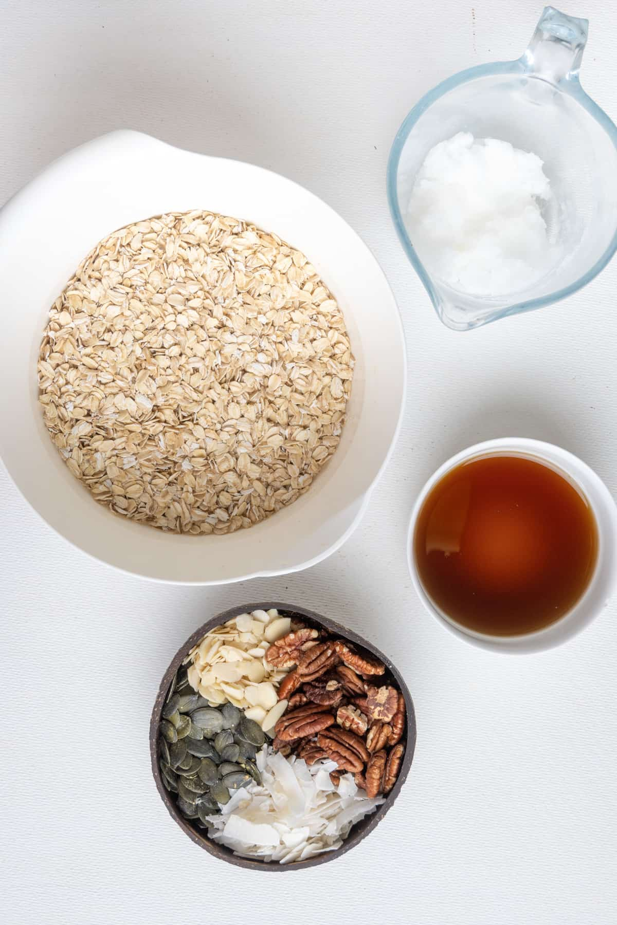 The ingredients for vegan granola: Rolled oats, nuts, mixed seeds and nuts, coconut oil and maple syrup.