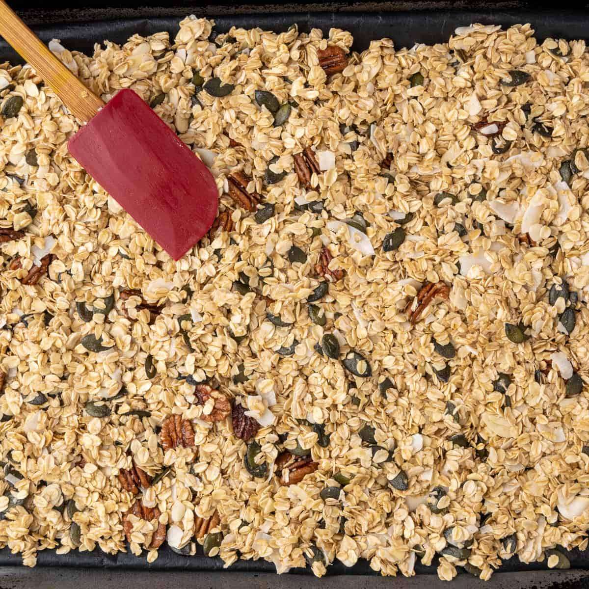 The granola mixture gets spread out on a baking tray.