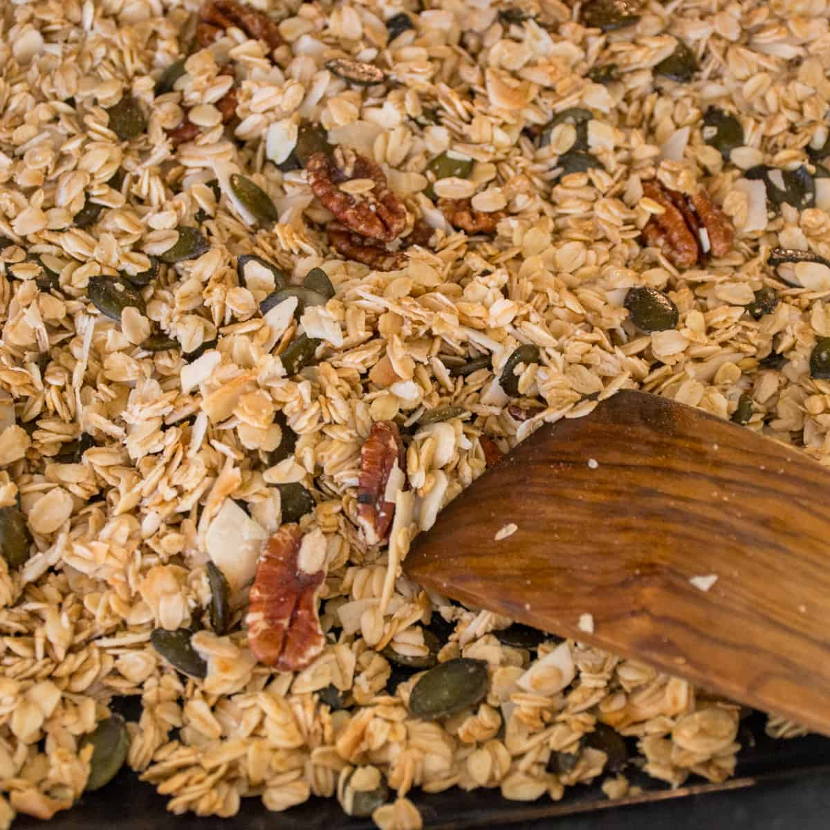 The granola gets stirred with a wooden spatula.