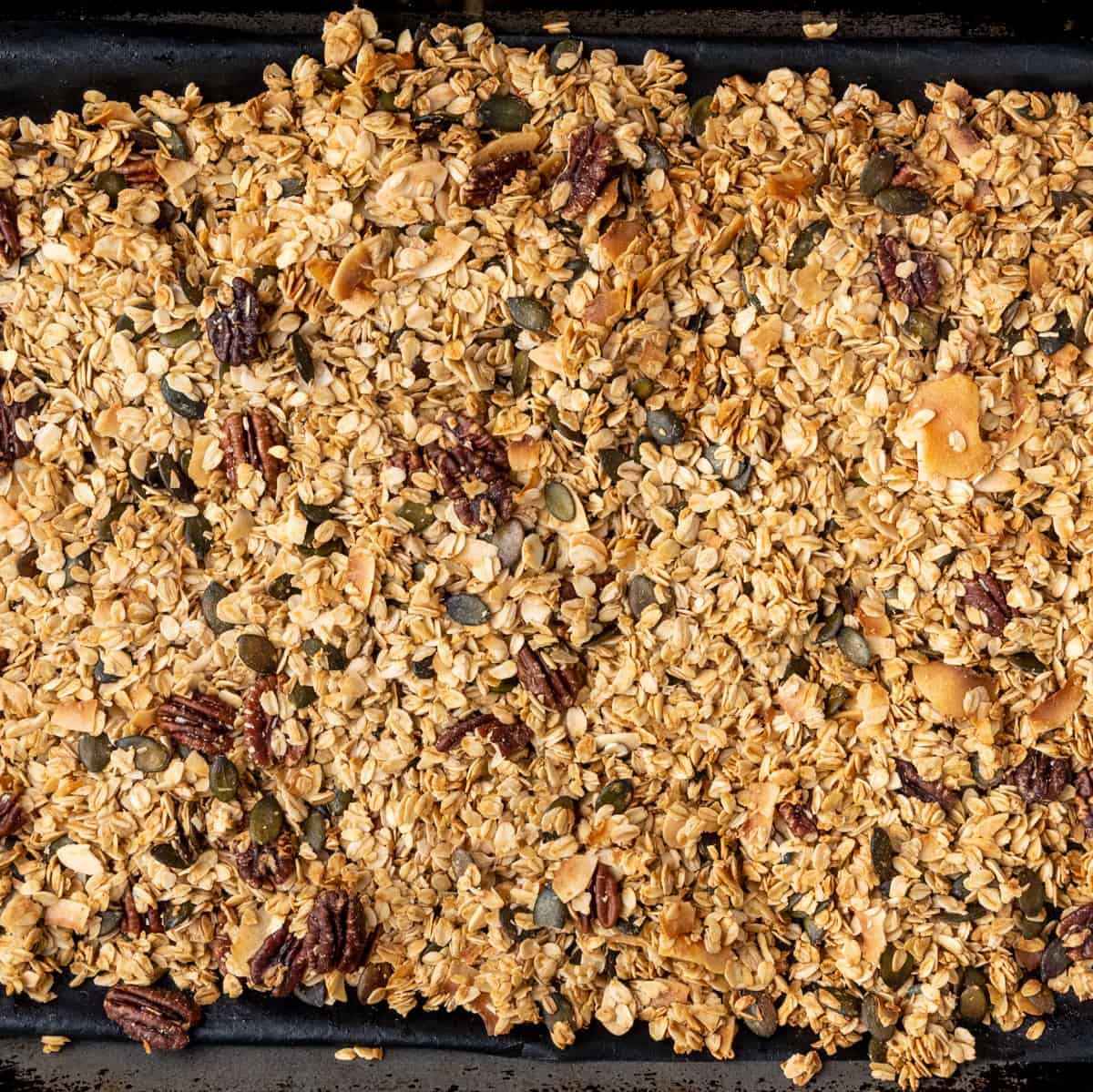 The tray of granola after baking to a golden brown colour.