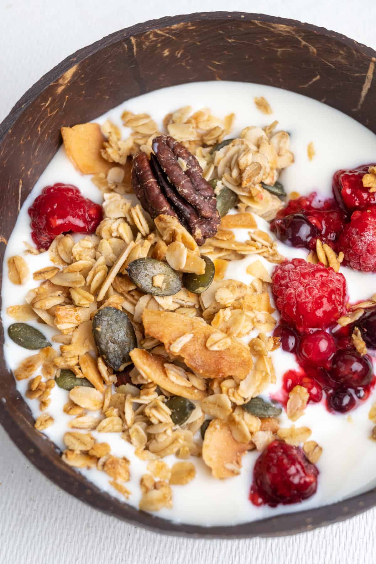 Granola and fresh red fruit on yoghurt in a coconut bowl.