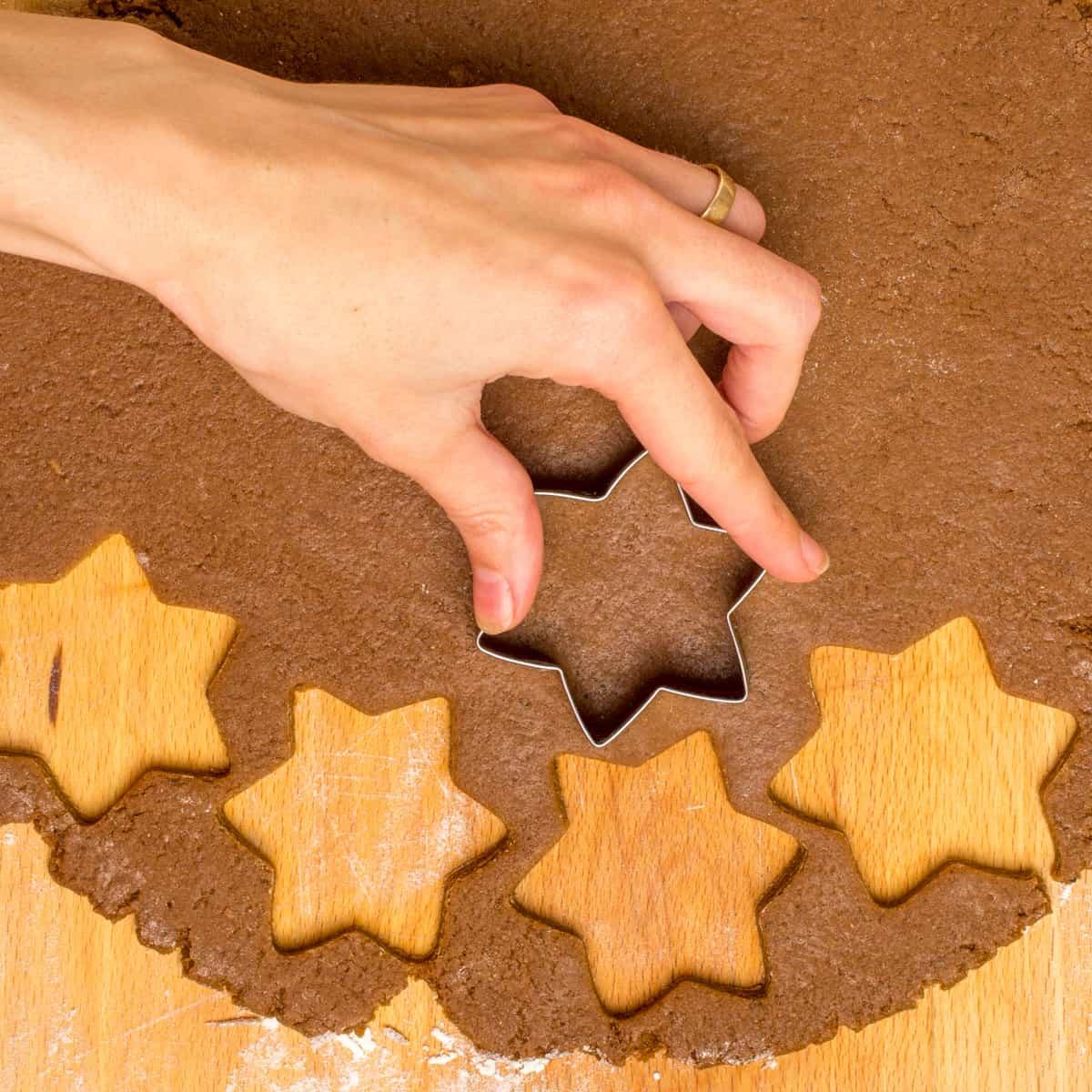 A hand cuts out stars from the rolled out dough.