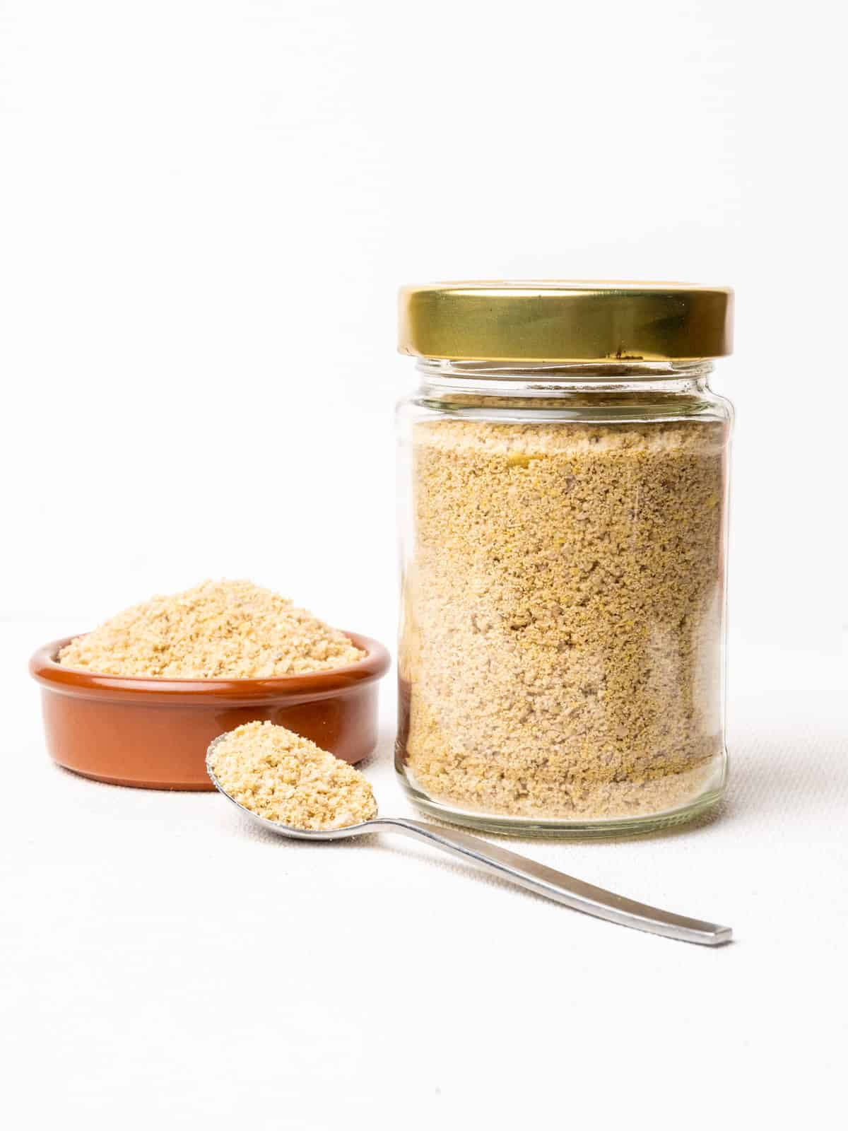 A jar, dish and spoon full of ground, pale yellow vegan alternative to parmesan cheese.