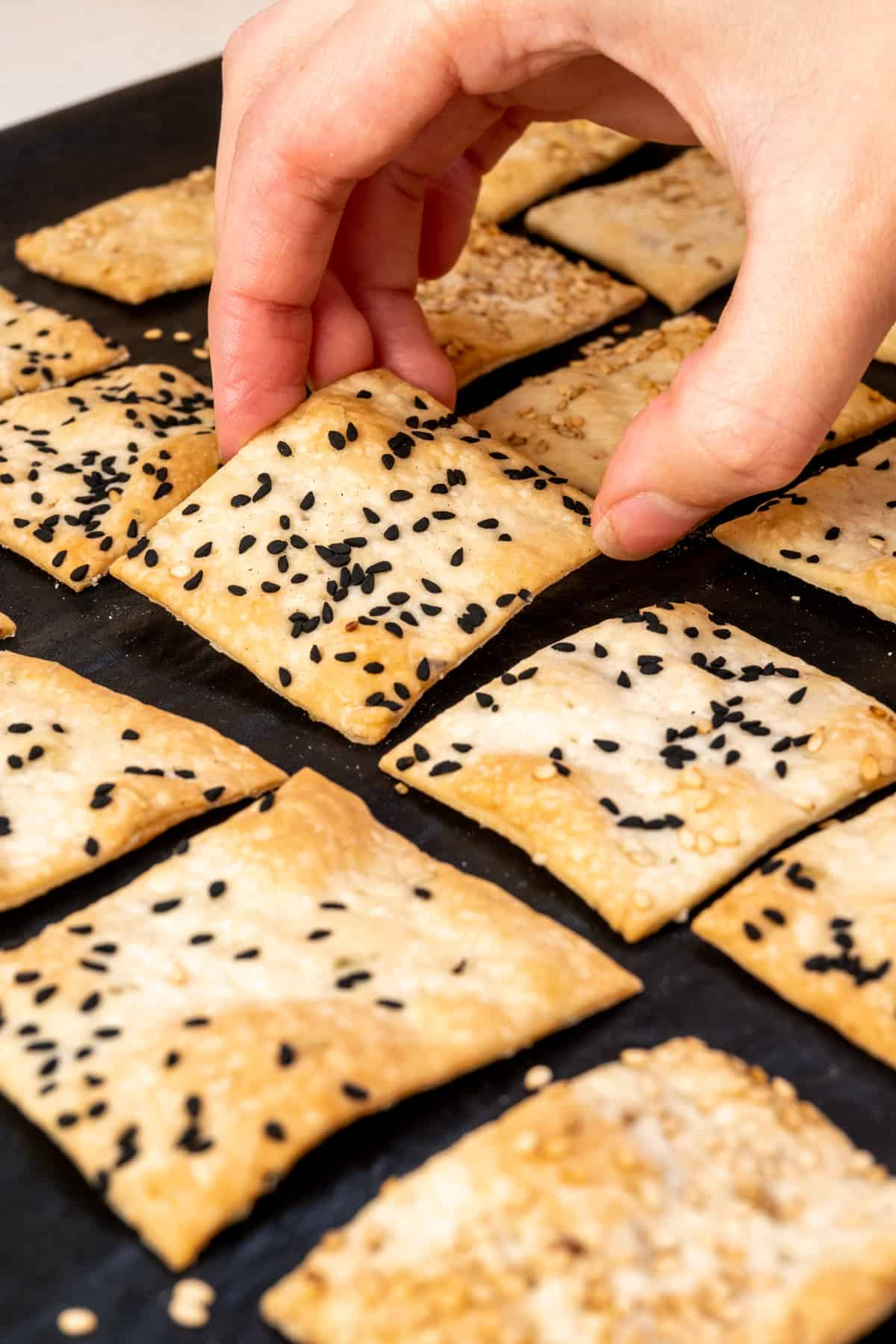 A hand picks up a freshly baked cracker from a baking tray.