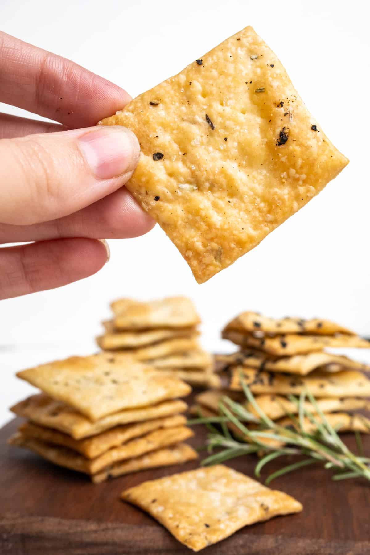 A hand holds up a golden brown cracker sprinkled with salt and pepper for a close up in front of a backdrop of more, stacked crackers.
