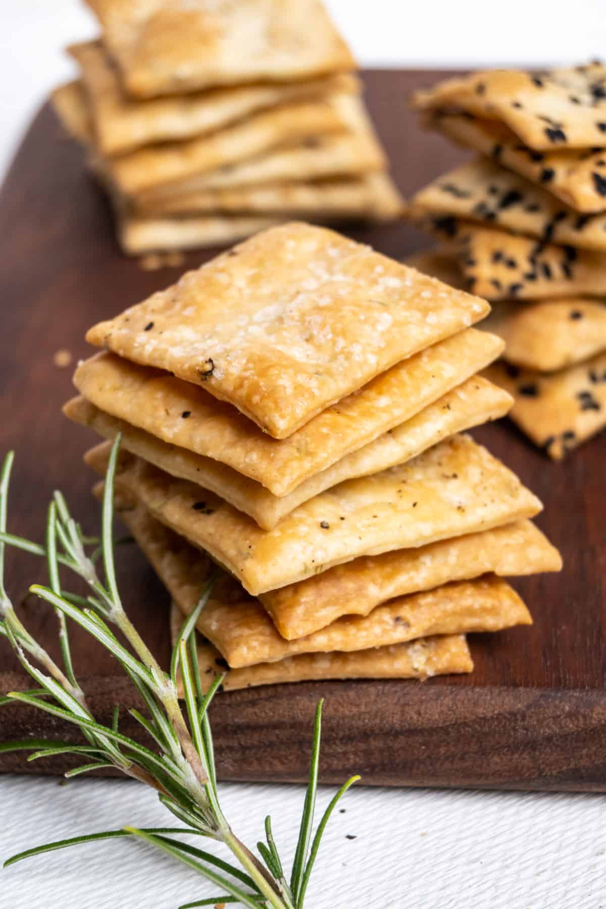 Stacks of homemade rosemary crackers, some topped with ground pepper and sea salt, some with sesame and nigella seeds.