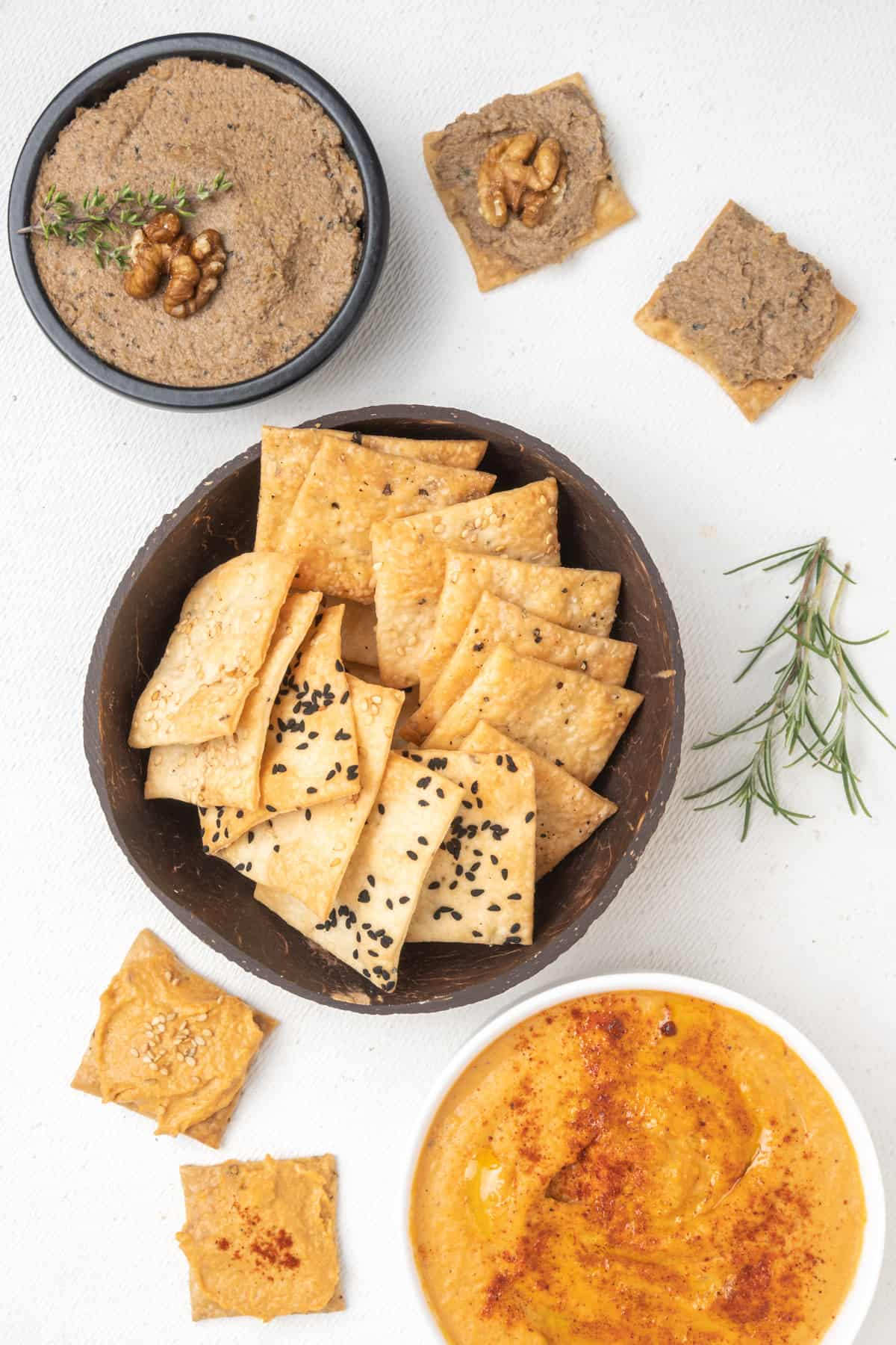 Crackers in a bowl served with two types of savoury dips: mushroom pate and grilled red pepper hummus.