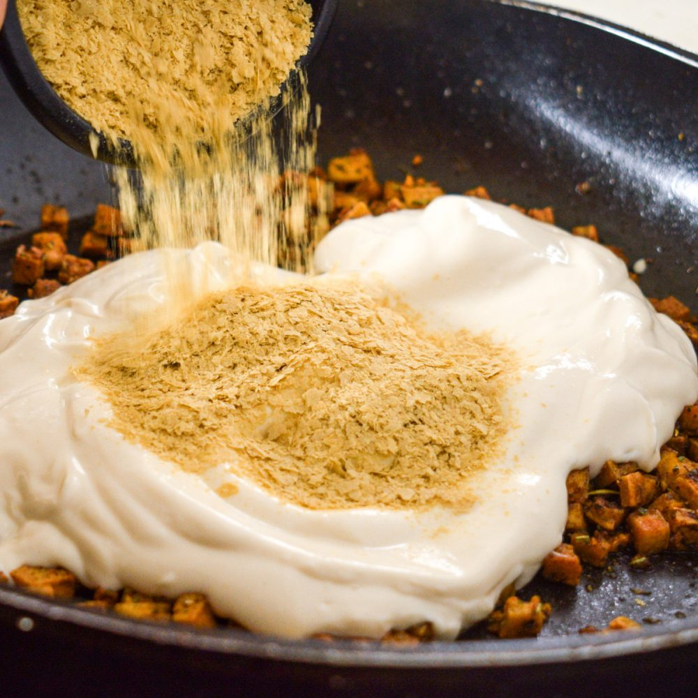 Adding nutritional yeast and blended silken tofu to make the creamy sauce.