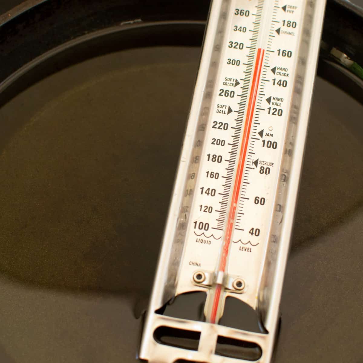 A thermometer in a pan of oil.