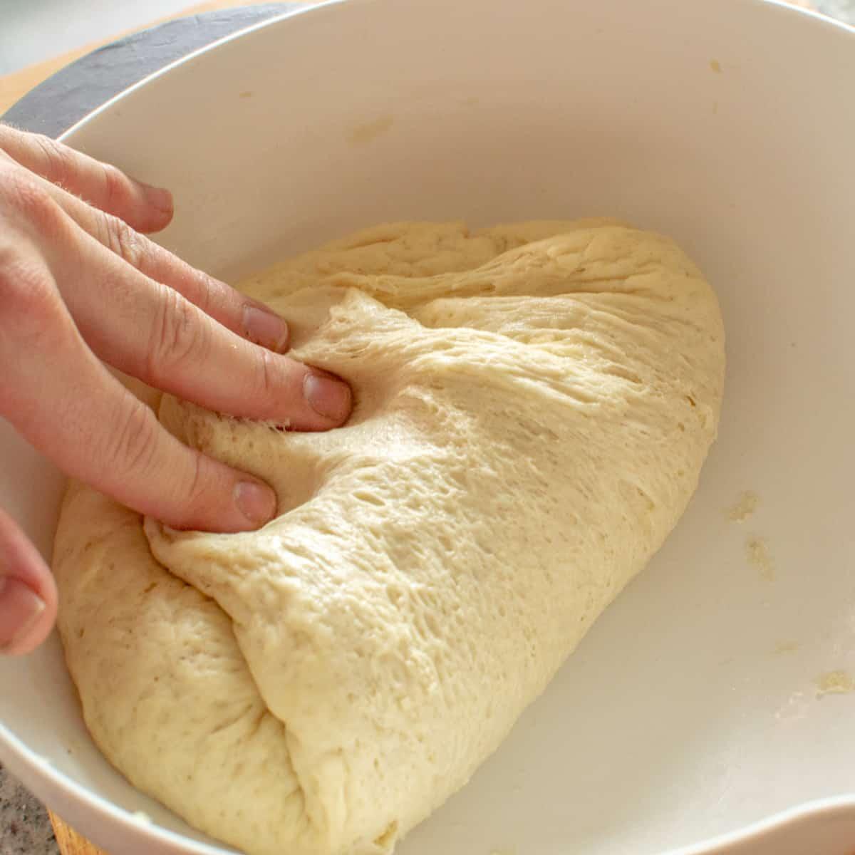 Folding the risen dough to knock it back.