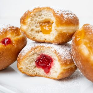 Two doughnuts with bites taken out, revealing the fluffy texture and jam filled centre.